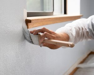 painter painting a wall white