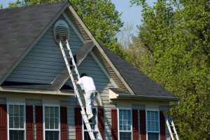 man on a ladder climbing on side of the house
